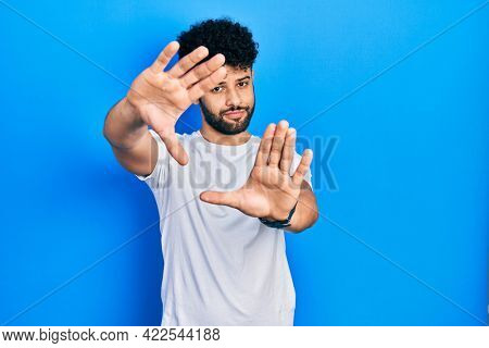 Young arab man with beard wearing casual white t shirt doing frame using hands palms and fingers, camera perspective