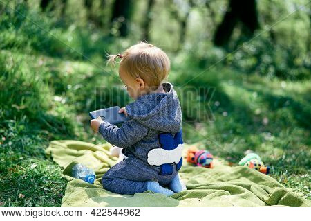 Little Girl Is Kneeling On A Green Blanket In A Meadow And Holding A Phone In Her Hands. Back View