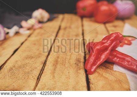 Peruvian Ingredients: Rocoto Chili Which Has Been Sliced On A Wooden Board, Chili Ají Limo, Garlic A