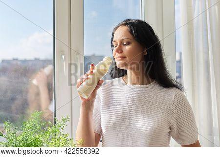 Woman Drinking Milk Drink From Bottle Standing Near Window, Milk Yogurt Dairy Healthy Drinks