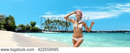 Hawaii beach vacation snorkel active happy Asian bikini girl coming out of swimming in ocean snorkeling fun. Panoramic banner with lava background.