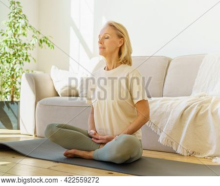 Peaceful Senior Woman In Lotus Position Meditation With Closed Eyes At Home While Sitting On Yoga Ma