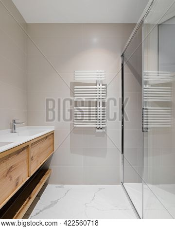 Modern Bathroom With Wooden Base For White Sinks. Radiator For Warm Water Procedures In Winter. Show