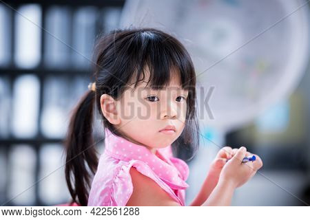 A 4 Year Old Asian Girl Is Holding A Blue Crayon In Her Hand. Child Is Turning His Attention To Some