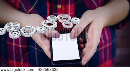 Composition of 3d cogs over midsection of woman using smartphone with copy space on screen. global business communication and networking technology concept digitally generated image.