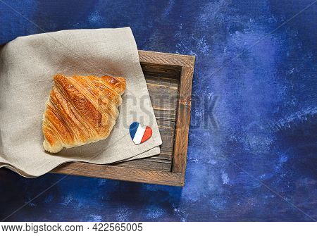 Fresh French Croissant And A Heart In The Colors Of The French Flag In Wooden Tray On Blue Backgroun