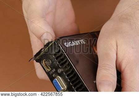 Graphics Card Brand Gigabyte Nvidia Geforce On A Brown Background. Man Holds Dusty Computer Componen
