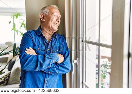 Senior man with grey hair leaning by the window of his home, smiling happy and confident looking outside