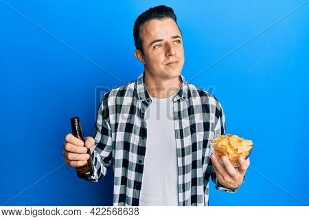 Handsome young man drinking a pint of beer holding chips smiling looking to the side and staring away thinking.
