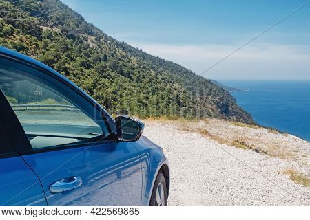 Blue Car Stopped Roadside Near The Sea On Sunny Day