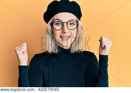 Young blonde girl wearing french look with beret celebrating surprised and amazed for success with arms raised and open eyes. winner concept.