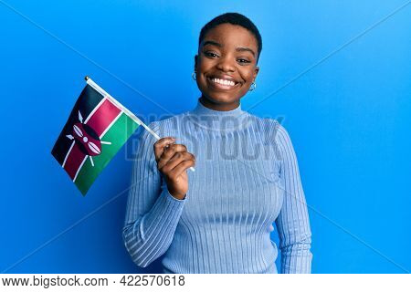 Young african american woman holding kenya flag looking positive and happy standing and smiling with a confident smile showing teeth