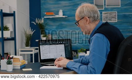 Senior Man Architect Analysing Digital Prototype With Plans From Laptop Working From Home, Taking No