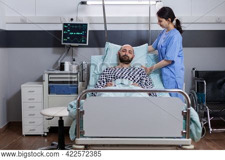 Medical Woman Asisstant Helping Patient To Sit Comfortable In Hospital Ward During Disease Consultat