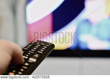 Close Up Of A Hand Holding Television Remote Control Which Switching Television Channels. Switching