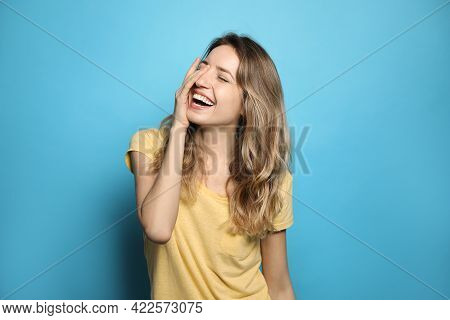 Cheerful Young Woman Laughing On Light Blue Background