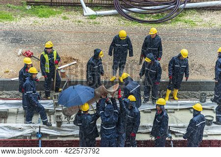 Tel Aviv, Israel - May 20 2021: Construction Workers Working In The Rain. Light Rail Tracks. Blue Co