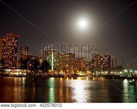 Full Large Moon Hangs Over Waikiki Hotels And Marina At Night As It Shimmers Off The Ocean On Oahu,