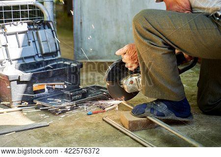 A Man Cuts A Titanium Tube With A Grinder
