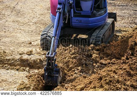 Mini Excavator Digging In Trench For The Foundation