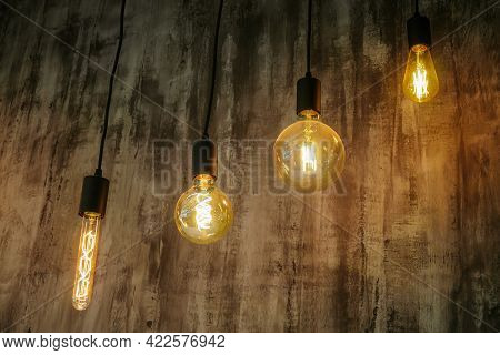Four Hanging Retro Incandescent Lamps. Vintage Glowing Light Bulbs.