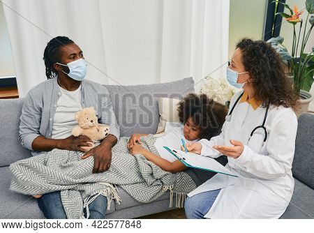 Medical Care At Home. Doctor Pediatrician Wearing A Protective Mask Visits A Little Girl Patient Who