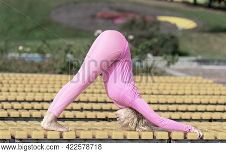 Pretty Young Woman Doing Yoga Asanas In The Park