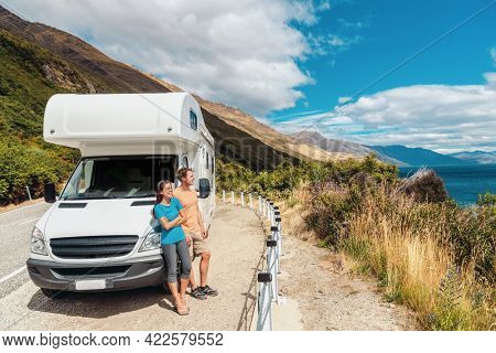 Motorhome RV camper van road trip on New Zealand. Young couple on travel vacation adventure. Two tourists looking at Lake Pukaki and mountains on enjoying view and break next to rental car