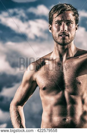 Strong fit muscular man with sexy six pack abs topless showing off toned body with cut stomach muscles. Fit model shredded abs male model with defined abs strength training. Cross light.