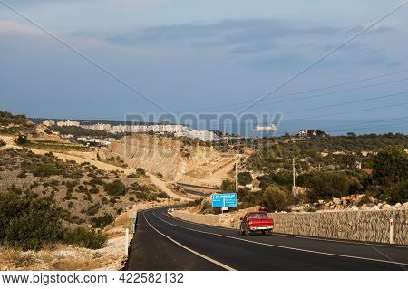 Evening View Onto Downhill Road In Mediterranean Region Of Turkey. Typical Resort City & Sea Are On