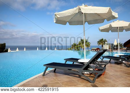 Chaise Longues And Beach Parasols Near Infinity Pool At Resort