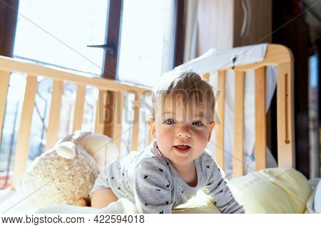 Little Kid Is Kneeling In A Wooden Crib Against The Background Of A Large Plush Sheep