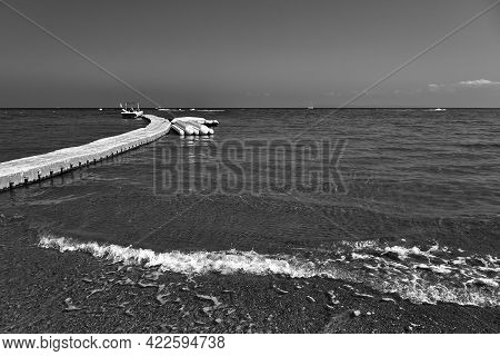 Floating Jetty With A Motorboat And Pontoons On The Beach On Zakynthos Island In Greece, Monochrome