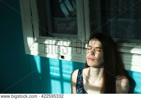 Young woman on the veranda of a country house.