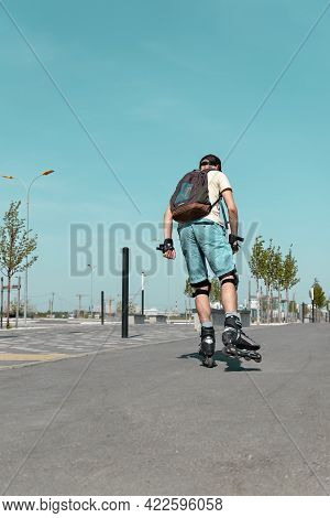 Rear View Of Young Man In Blue Shorts With Backpack, In Protective Equipment Riding On Roller Skates