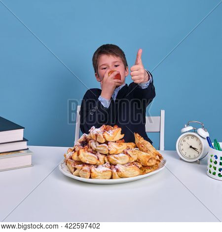 Pupil Boy Junior With An Apple In His Hands Shows A Gesture Of Approval Of Healthy And Wholesome Foo