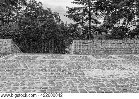 Fence And Staircase Made Of Granite Stones. A Cobbled Area With A Stone Cobblestone Fence. Observati