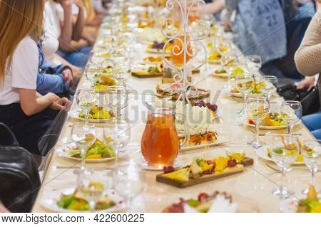 A Feast In A Cafe, A Russian Holiday, The Table Is Covered With Glasses, Fruit, Plates With Salad.