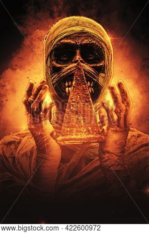 Portrait of a scary egyptian mummy holding a pyramid in his hands surrounded by flames. Halloween. Ancient Egyptian mythology.