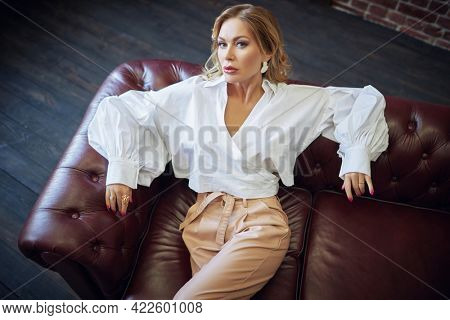 Glamorous middle-aged woman with enlarged full lips, evening makeup and bright manicure lying on a leather sofa. Luxury lifestyle. High fashion shot.