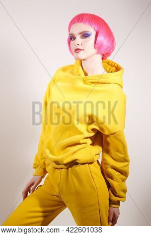High fashion model with bright glitter make-up and pink hair poses at studio in trendy yellow clothes. Make-up and hairstyle. Sport chic clothing. Party style.