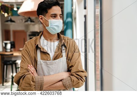 Close up of a hispanic young man waiter in protective medical mask and apron standing in cafe indoors