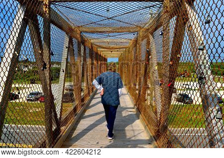 Unrecognizable Person Walking Across Bridge With Love Locks In The Background. Symbol Of Couples Ete