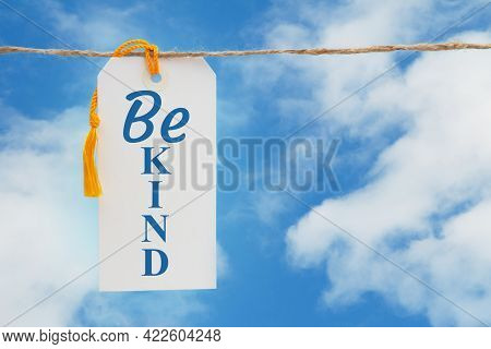 Be Kind Message White Gift Tag With Yellow Ribbon Over Sky