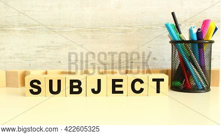 Seven Stacked Wooden Cubes With Letters Subject On A White Work Table On A Gray Background. Business