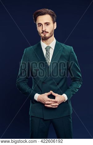Men's fashion. Portrait of a handsome man in elegant suit and a tie posing on a dark blue background.