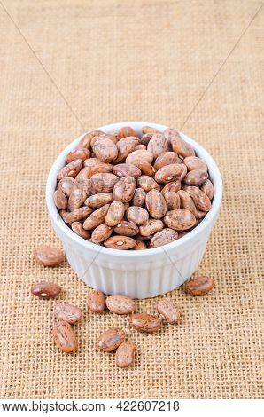 Raw Organic Cranberry Beans In White Cup On Sack Background.