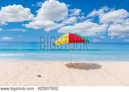 A Colourful Umbrella On White Beach With Beautiful Sky In Summer.