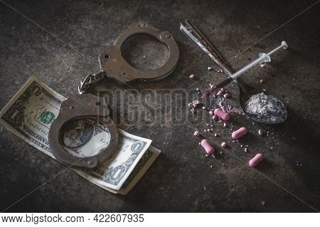 Drug Syringe And Cooked Heroin On Spoon And Handcuffs . Concept - Punishment For Possession Of Narco