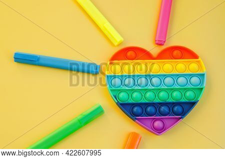 Top view of colorful markers and anti stress sensory toy pop it rainbow heart on yellow background c